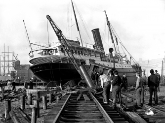 A ship uprooted from the water lays across railroad tracks in New London, Connecticut. (Credit: Getty Images)