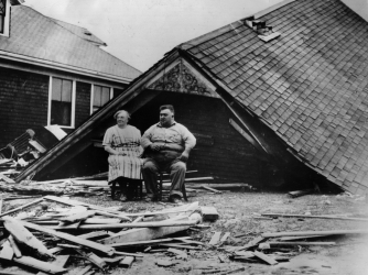 A couple sitting amongst the remains of their home at Highland Park, Rhode Island. (Credit: Getty Images)