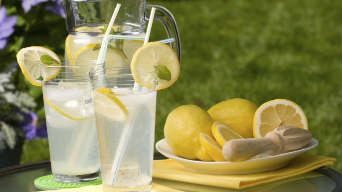 Two glasses of home made iced cold lemonade and pitcher on hot summer. Copyspace