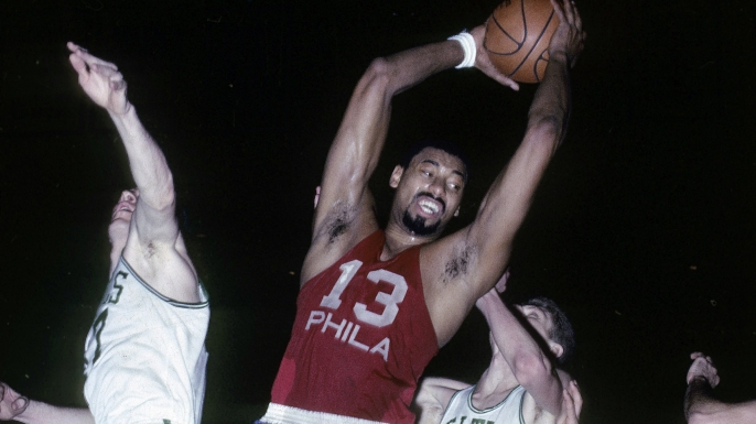 Wilt Chamberlain of the Philadelphia 76ers pulls down a rebound against the Boston Celtics during a mid-1960s game at Boston Garden. (Credit: Focus on Sport/Getty Images)