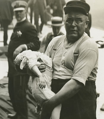 Chicago fireman Leonard Olson rescuing a child. (Credit: Jun Fujita/Chicago History Museum/Getty Images)