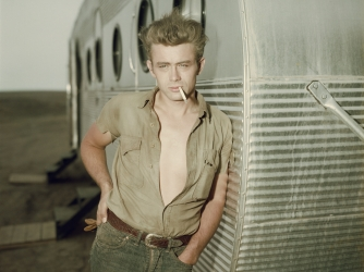 James Dean leaning against a dressing room trailer on the set of director George Stevens's film, 'Giant,' in 1955. (Credit: Hulton Archive/Getty Images)