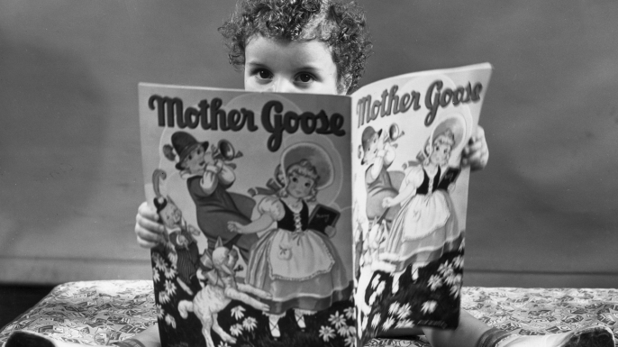 A young girl sits on top of her bed, reading a Mother Goose storybook. (Credit: Harold M. Lambert/Lambert/Getty Images)