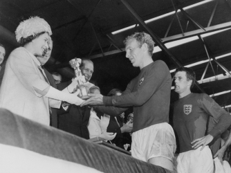 Queen Elizabeth II presents the trophy to Bobby Moore, captain of England's national team. (Credit: STAFF/AFP/Getty Images)