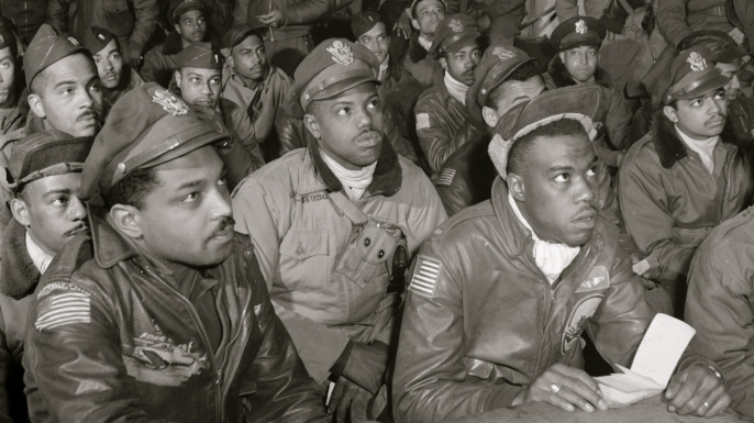 "Tuskegee airmen attending a briefing in Italy in 1945. First row (l-r): Hiram E. Man, unidentified airman, Newman C. Golden, Bertram W. Wilson Jr., Samuel W. Watts Jr., Second row (l-R): Armour G. McDemoe, Howard C. Gamble, Harry T. Steward, Jr, Earle R. Lane, Wickliffe, Wyrain T. Shell, Harold M. Morris, John E. Edwards, John H. Porter, James H. Fischer, Wyrain T. Shell. Third row (l-r): William E. ""Porky"" Rice, Tony Weaver, Charles L. White, George Arnold Lynch, Samuel L. Washington, Calvin J. Spann, Frank N. Wright. (Credit: Buyenlarge/Getty Images)"