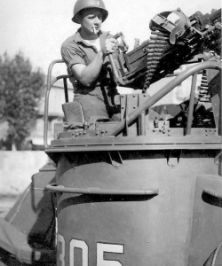 "An unidentified serviceman handles PT-305's port-side .50-caliber Browning machine gun, or ""gun tub."" (Gift of Cathy Kaminski/Courtesy of The National WWII Museum)"