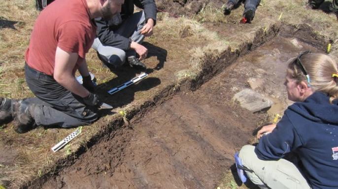Douglas Bolender (L) and Sarah H. Parcak (R) looking for evidence of a Viking presence at Point Rosee. (Credit: Greg Mumford)