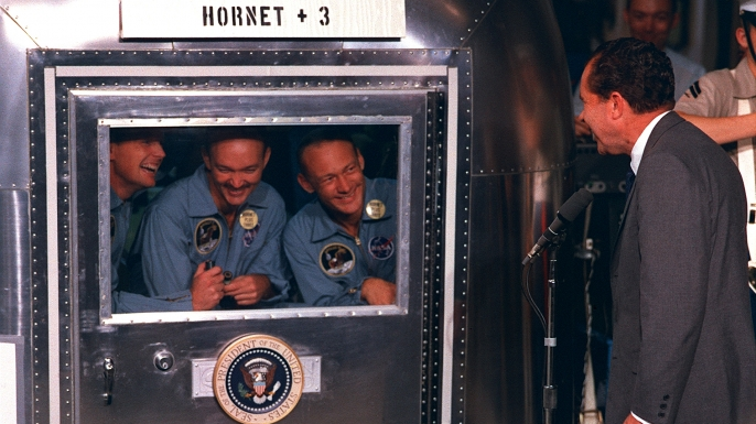 """President Richard M. Nixon was in the central Pacific recovery area to welcome the Apollo 11 astronauts. Already confined to the Mobile Quarantine Facility (MQF) are (left to right) Neil A. Armstrong, commander; Michael Collins, command module pilot; and Edwin E. (""""Buzz"""") Aldrin Jr., lunar module pilot. (Credit: NASA)"""