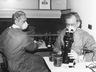 This historic photograph depicted Centers for Disease Control (CDC) laboratorian George Gorman at left, along side Dr. Jim Feeley, while they were examining culture plates with the first environmental isolates of Legionella pneumophils. (Credit: Public domain)