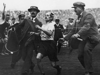 Dorando Pietri of Italy, on the verge of collapse, is helped across the finish line in the Marathon event of the Olympic Games in London, 1908. He was subsequently disqualified. (Credit: Public Domain)