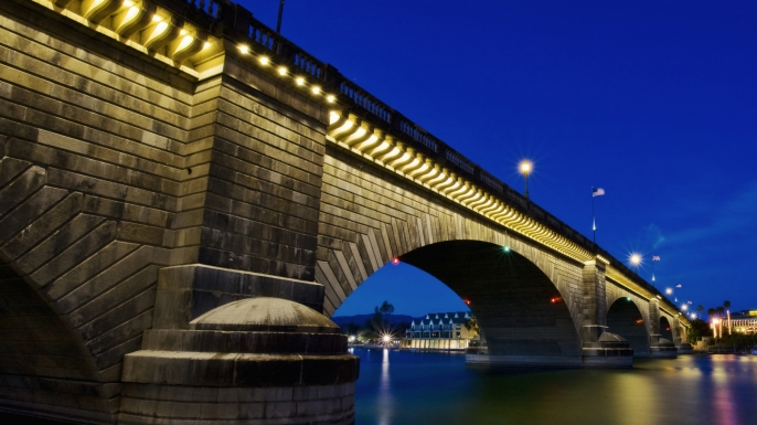 London Bridge at night, spanning the waters of Lake Havasu. (Credit: Mint Images / Getty Images)