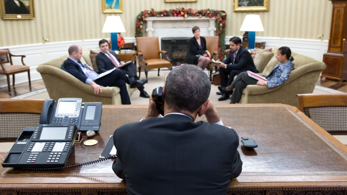 President Barack Obama talks on the phone during a National Security Council (NSC) call in the Oval Office, Dec. 16, 2014. (Official White House Photo by Pete Souza)