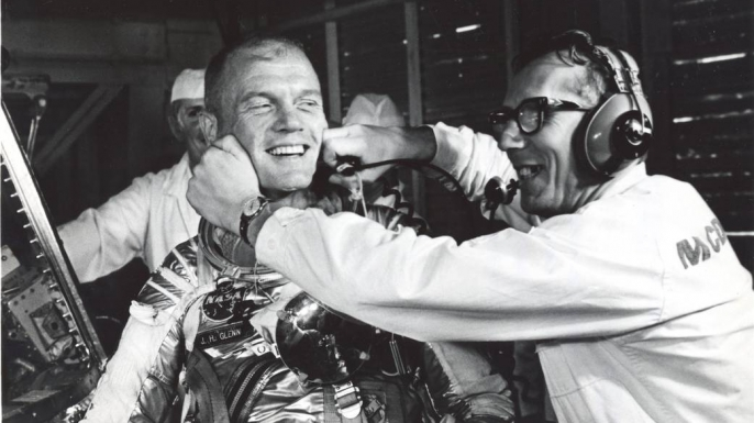Guenter Wendt, the original pad leader for NASA's manned programs, coaxes a smile from Glenn after a postponement of the mission. (Credit: NASA)