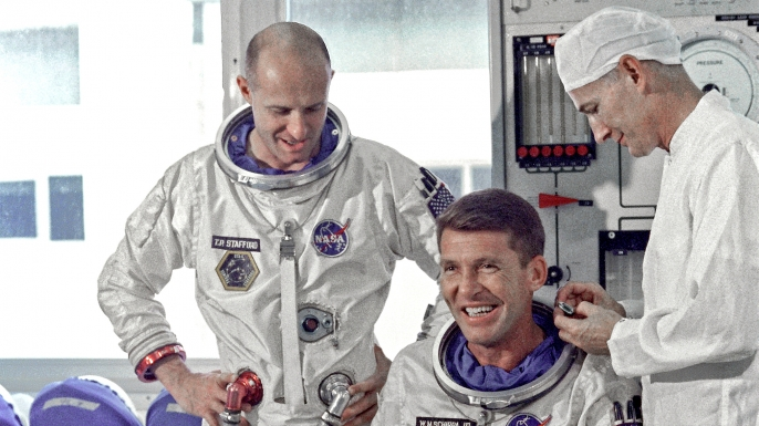 Astronauts Walter M. Schirra Jr. (seated), command pilot, and Thomas P. Stafford, pilot, Gemini 6 prime crew, go through suiting up exercises in preparation for their forthcoming flight. (Credit: Public Domain)