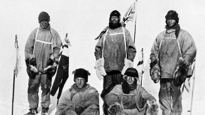 Robert Falcon Scott's Pole party of his ill-fated expedition, from left to right at the Pole: Oates (standing), Bowers (sitting), Scott (standing in front of Union Jack flag on pole), Wilson (sitting), Evans (standing). Bowers took this photograph, using a piece of string to operate the camera shutter. (Credit: Public Domain)