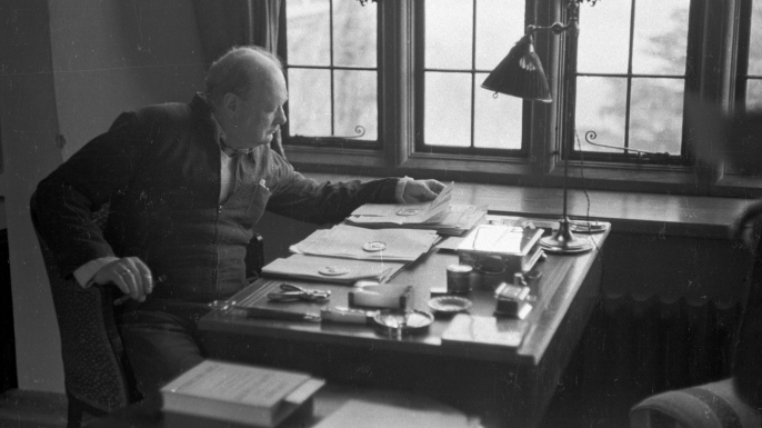 Churchill sits at the writing desk of his country home in 1939.