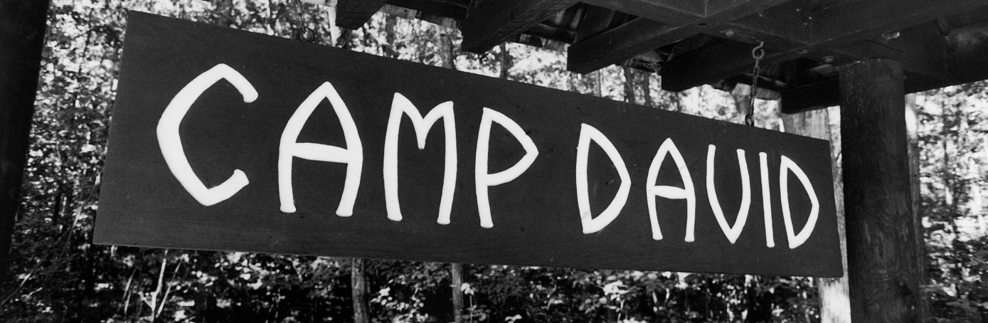 Wooden sign w. CAMP DAVID painted in white letters.