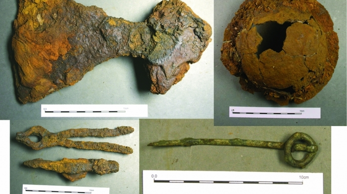 Some of the artifacts recovered from the burial site (clockwise from the top left): broad-bladed axe, shield boss, ringed pin and the hammer and tongs (Credit: Pieta Greaves/AOC Archaeology).
