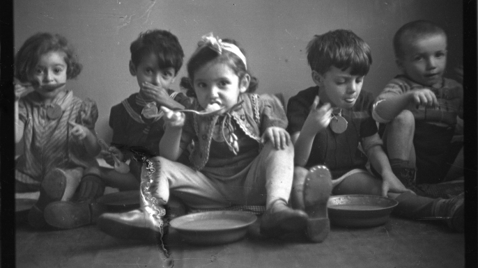 Five children siting on floor and eating, 1940-1944.