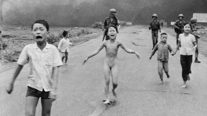 South Vietnamese forces follow after terrified children, including 9-year-old Phan Thi Kim Phuc, center, as they run down Route 1 near Trang Bang after an aerial napalm attack on suspected Viet Cong hiding places.