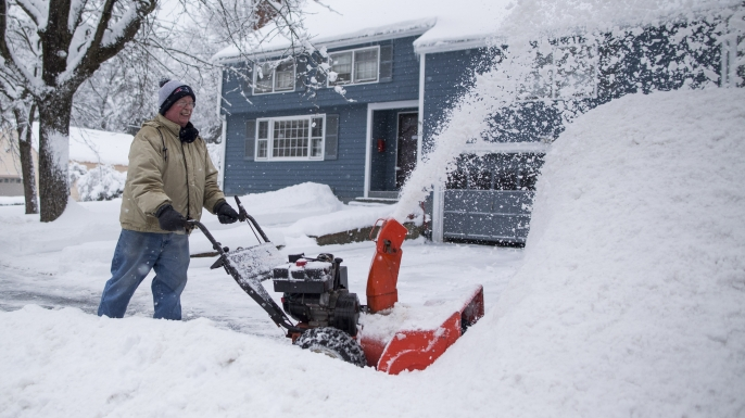 A man uses a snowblower to clear his driveway.  (Credit: Scott Eisen/Getty Images)