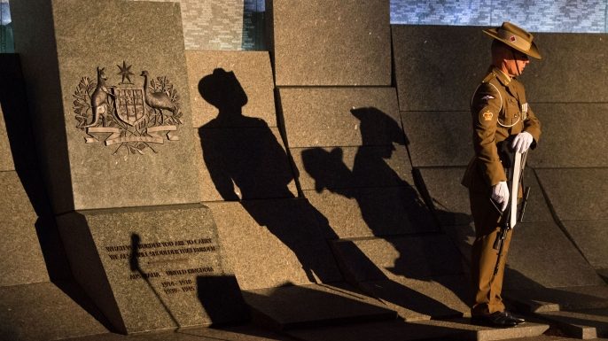 An Australian soldier stands at the Australian War Memorial during an Anzac Day dawn service at Hyde Park Corner in London on April 25. (Credit: DOMINIC LIPINSKI/AFP/Getty Images)