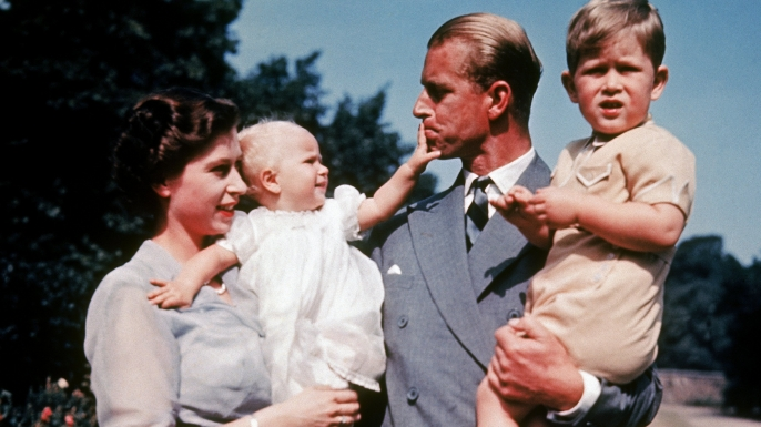 Queen Elizabeth holding daughter Anne and Prince Philip holding son Charles.