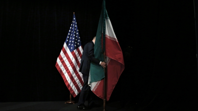 A staff removes the Iranian flag from the stage after a group picture with foreign ministers and representatives of Unites States, Iran, China, Russia, Britain, Germany, France and the European Union during the Iran nuclear talks at Austria International Centre in Vienna, Austria on July 14, 2015. Major powers clinched a historic deal aimed at ensuring Iran does not obtain the nuclear bomb, opening up Tehran's stricken economy and potentially ending decades of bad blood with the West. AFP PHOTO / POOL / CARLOS BARRIA / AFP / POOL / CARLOS BARRIA