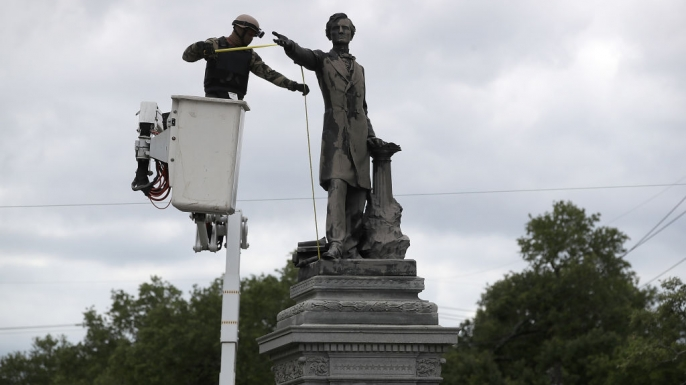 A New Orleans city worker wearing body armor and a face covering as he prepares the Jefferson Davis monument on May 4, 2017.