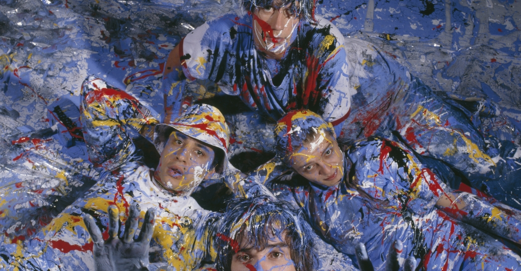 """Manchester rock group The Stone Roses in a paint-spattered abstract expressionist romp. Formed in Manchester in 1983, they were pioneers of the """"Madchester"""" movement. (Credit: Kevin Cummins/Getty Images)"""