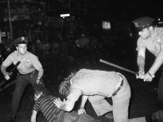 A NYPD officer grabs a youth by the hair as another officer clubs a young man during a confrontation in Greenwich Village after a Gay Power march in New York, 1970. (Credit: Associated Press)