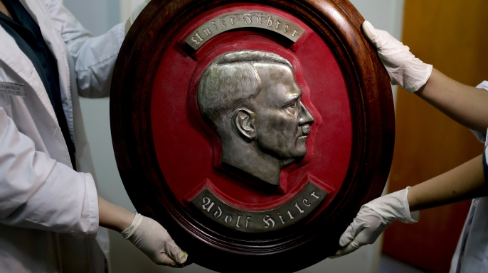 Members of the federal police show a bust relief portrait of Nazi leader Adolf Hitler at the Interpol headquarters in Buenos Aires, Argentina, Friday, June 16, 2017. In a hidden room in a house near Argentina's capital, police discovered on June 8th the biggest collection of Nazi artifacts in the country's history. Authorities say they suspect they are originals that belonged to high-ranking Nazis in Germany during World War II. (Credit: AP Photo/Natacha Pisarenko)