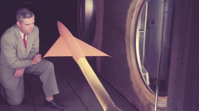 NACA member Charles Hall studies a model aircraft.