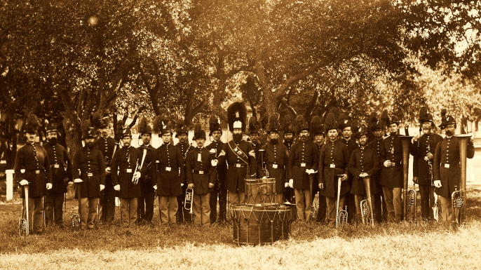 Group portrait of the band, 24 uniformed men, many of whom are holding musical instruments, Fort Monroe, VA, 1864. They are wearing hats with plumes. (Credit: Buyenlarge/Getty Images)