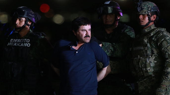 """Joaquin """"El Chapo"""" Guzman, the world's most wanted-drug trafficker, center, is escorted by Mexican security forces at a Navy hangar in Mexico City, Mexico, on Friday, Jan. 8, 2016. (Credit: Susana Gonzalez/Bloomberg via Getty Images)"""