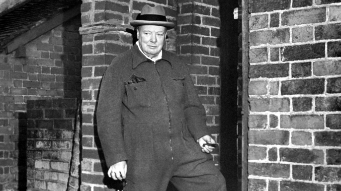 Winston Churchill relaxing in a siren suit smoking a cigar. (Credit: Jeremy Moeran / Alamy Stock Photo)