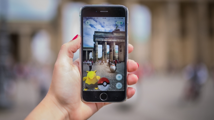 A woman points her smart phone at the Brandenburg Gate as she plays the Pokemon Go mobile game. (Credit: SOPHIA KEMBOWSKI/AFP/Getty Images)