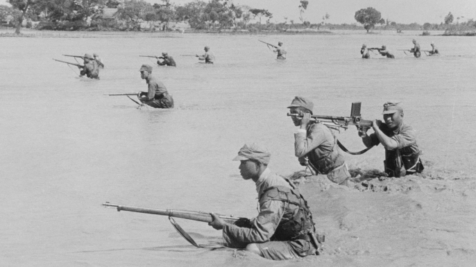 Holding their lines to the utmost against Japanese, the defenders refused to retreat when the Yellow River began flooding. Here, through the muddy stream, a Chinese advance guard braves flood and enemy fire. (Credit: Bettmann/Getty Images)