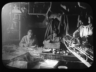 Fougner, Evans and Colbeck working inside the hut in November 1899.