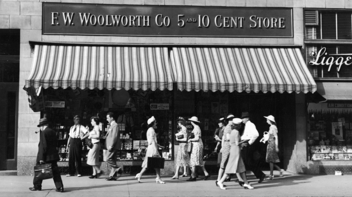 People walk past an F.W. Woolworth five and dime store on a city street, 1940s. (Credit: Martin Forstenzer/Getty Images)