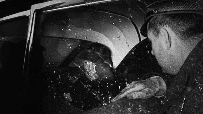 Serial Killer Ed Gein sitting in back of police car after being arrested. He supposedly murdered 11 people, eviscerating them and hiding body parts in his house. (Credit: Frank Scherschel/The LIFE Picture Collection/Getty Images)