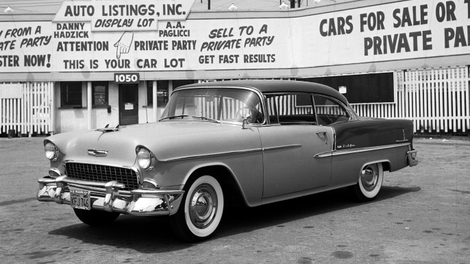 Two-tone 1955 Chevrolet Bel Air with whitewall tires in a used-car lot. (Credit: Eric Rickman/The Enthusiast Network/Getty Images)
