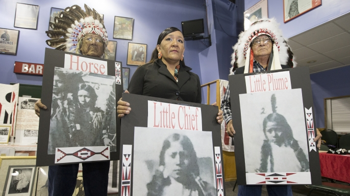 Yufna Soldier Wolf, center, of the Northern Arapaho, with tribal elders, Mark Soldier Wolf and Crawford White Sr., holds pictures of the three Arapaho children buried at the Carlisle Indian School. Experts made final preparations August 7, 2017, to exhume bodies of three Native American children named Little Plume, Horse and Little Chief who died about 135 years ago while attending a government-run school in Pennsylvania, and return the bodies to Wyoming. (Credit: Charles Fox/The Philadelphia Inquirer/AP Photo)