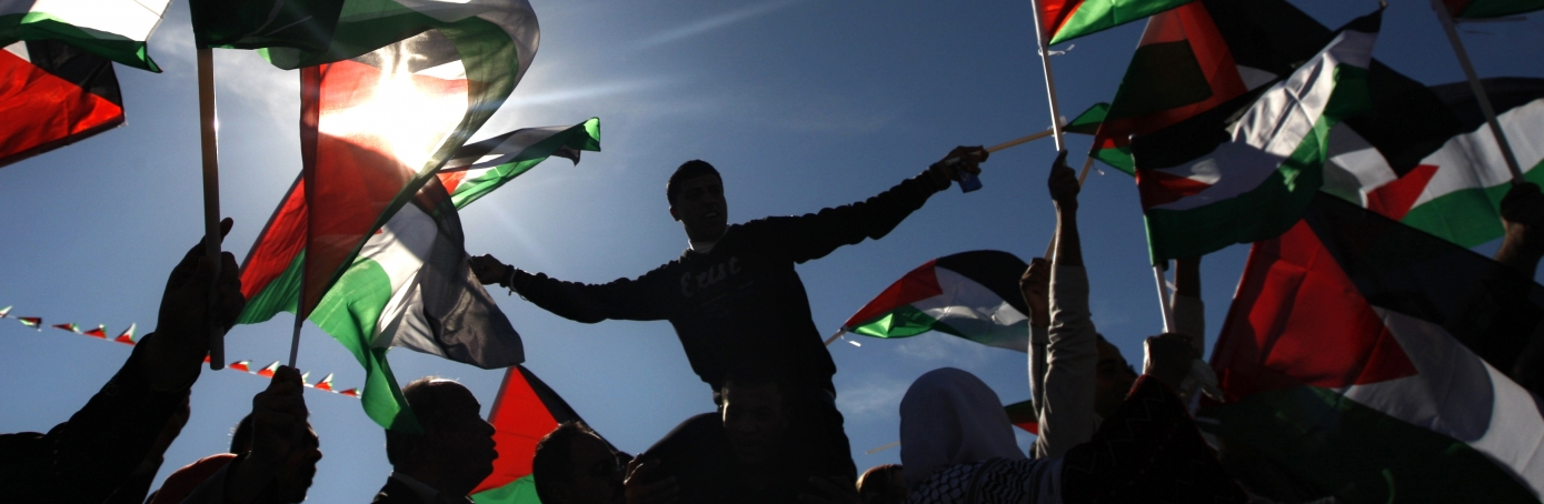 Palestinians wave flags as they celebrate their successful bid to win U.N. statehood recognition in the West Bank city of Ramallah, 2012. (Credit: Majdi Mohammed/AP Photo)