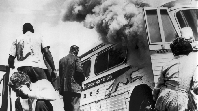 Freedom Riders on a Greyhound bus, sponsored by the Congress of Racial Equality (CORE), sit on the ground outside the bus after it was set afire by a group of white protestors upon their arrival in Anniston, Alabama. (Credit: Underwood Archives/Getty Images)