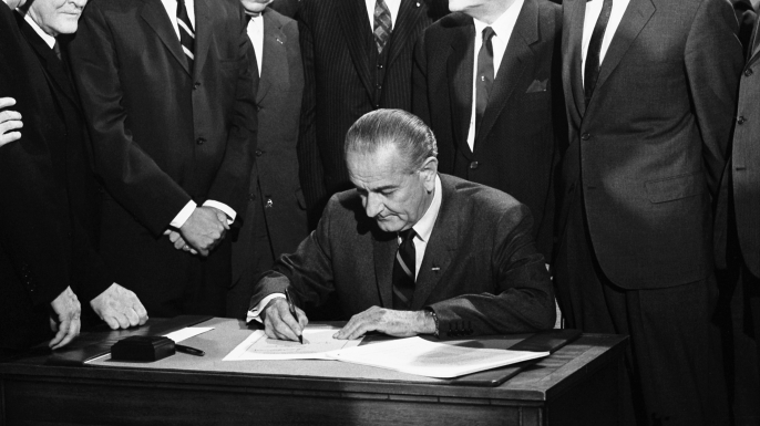 On April 11, 1968 President Lyndon Johnson signs the Civil Rights bill while seated at a table surrounded by members of Congress, Washington DC. (Credit: Warren Leffler/Underwood Archives/Getty Images)