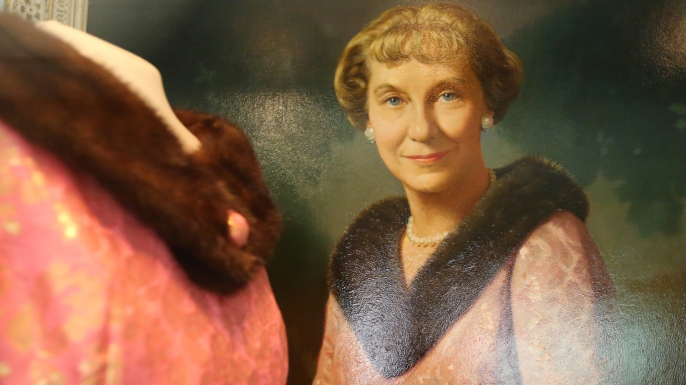 An oil painting of Mamie Eisenhower hangs beside the fur collared gown she wore for the portrait, at the Eisenhower Library in Abeline, Kansas. (Credit: Bo Rader/Wichita Eagle/TNS via Getty Images)