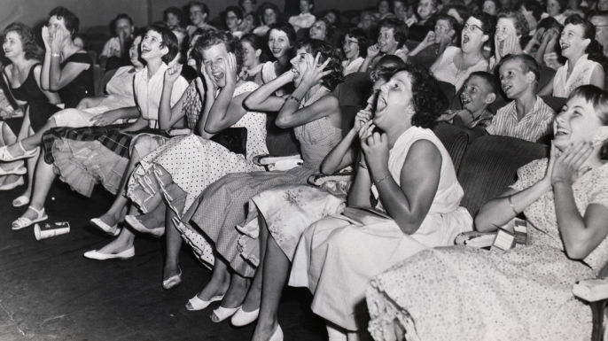 At a theater, fans of Elvis Presley gather to watch the world premier of his film Loving You. (Credit: Bettmann/Getty Images)