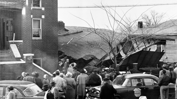 Onlookers surround the home of Rev. Fred Shuttleworth, which was destroyed by a dynamite blast. The Reverend's wife and two children were injured in the explosion. (Credit: Bettmann/Getty Images)