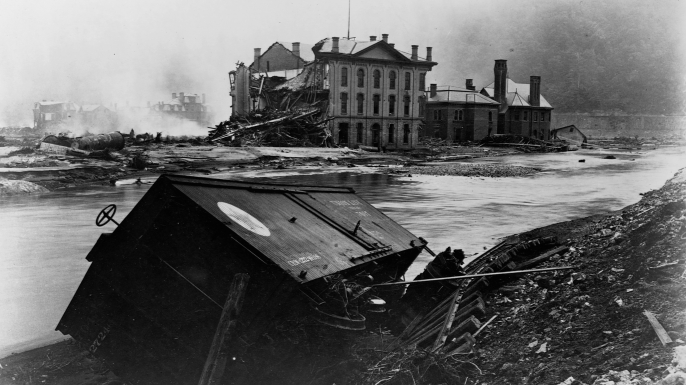 A wrecked freight car next to twisted railroad tracks, after the Johnstown, Pennsylvania flood of 1889. The warehouse of the Cambria Iron Works Company in the back was severely damaged. (Credit: Library of Congress/Corbis/VCG via Getty Images)